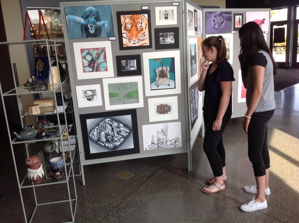 Freshmen Cristina Shaffer and Ali Lo contemplate the artwork of their peers. Photo by Jeanne Hanigan