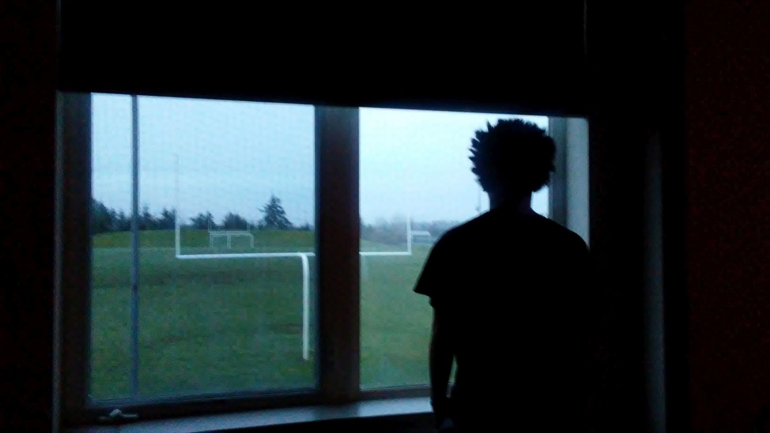 Nate Thomas looks out the window overlooking Memorial Field. Photo courtesy of Annette Thomas