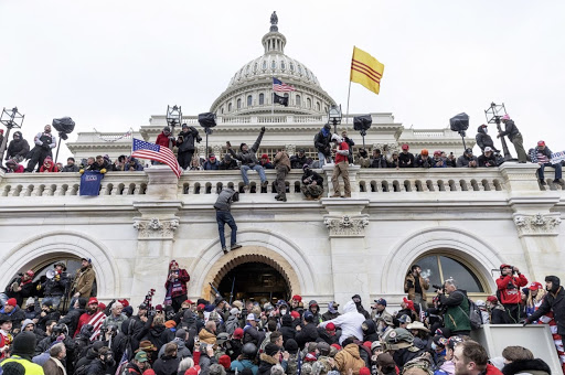Hundreds of rioters storm the Capitol building, clashing with law enforcement, and climbing the walls. Lev Radin / Pacific Press/LightRocket via Getty Images.