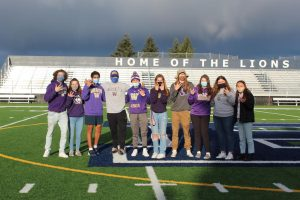 The seniors attempt the W sign to represent the University of Washington.